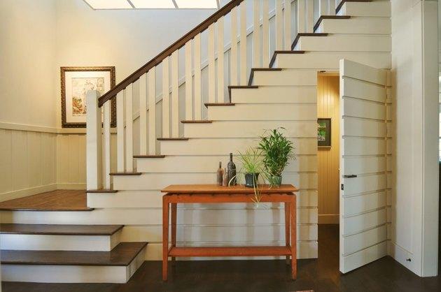 Powder room didesain seolah tersembunyi di bawah tangga, karya Alchemy Interiors